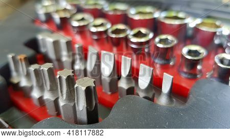 Rows Of Various Shape Bits In Red Box. Steel Drill Set. Tools Closeup. Selective Focus Toolkit Of Bi