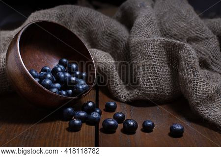 Ripe Blueberry Pouring Out From Wooden Bowl On Brown Background With Burlap Cloth. Rustic Still Life
