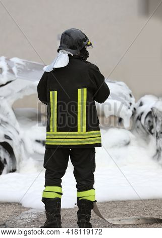 Firefighter Extinguishing A Fire A Damaged Car With The Foam After The Car Accident