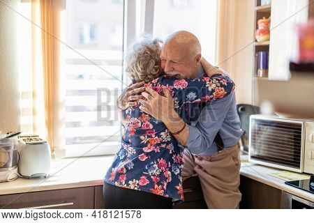 Elderly couple embracing and smiling in the kitchen