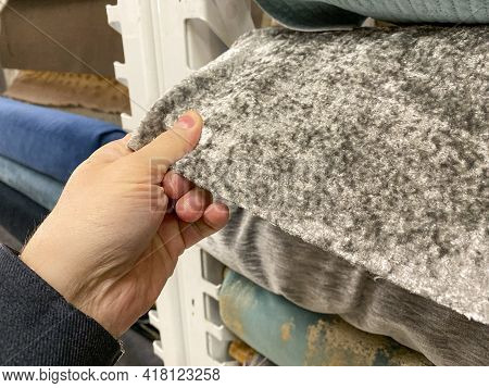 Person Looking At Different Fabrics At A Store, Shopping For Fabric Or Rugs