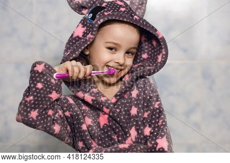 Cheerful Little Girl In A Hooded Robe Brushes Her Teeth With Toothpaste And Has Fun After Eating. De