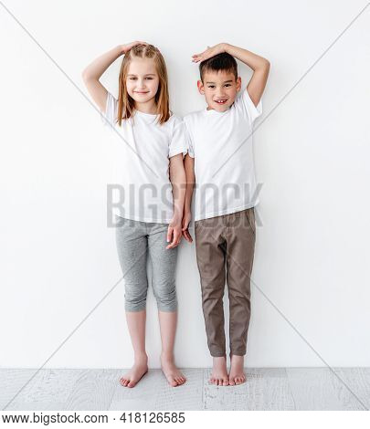 children measuring height and comparing on white wall background