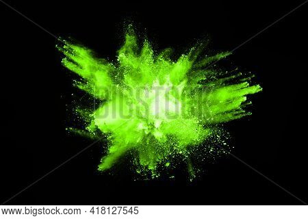 The Movement Of Abstract Dust Explosion Frozen Green On Black Background. Stop The Movement Of Powde