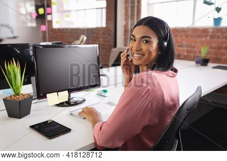 Happy mixed race businesswoman having video call sitting in front of computer using headphones. independent creative design business.