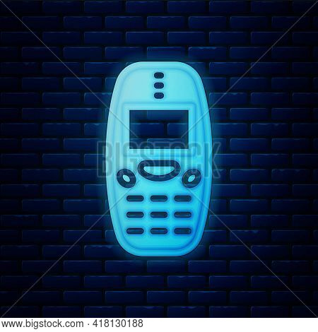Glowing Neon Old Vintage Keypad Mobile Phone Icon Isolated On Brick Wall Background. Retro Cellphone