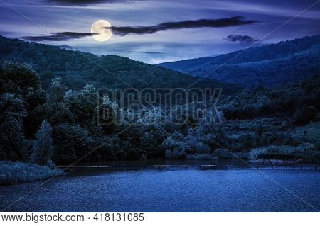 Mountain Scenery With Lake In Spring At Night. Wonderful Rural Landscape With Deciduous Trees On The
