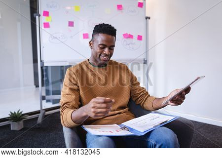 Happy african american businessman sitting having video call on tablet with whiteboard in background. independent creative design business.