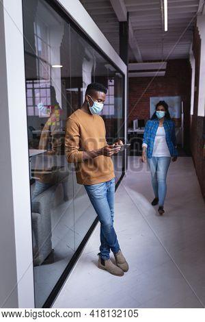 Diverse male and female colleagues wearing face mask standing in corridor. independent creative design business during covid 19 coronavirus pandemic.