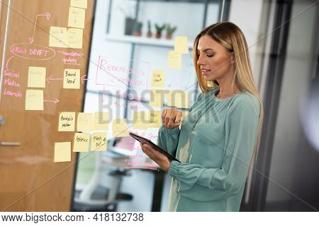 Caucasian businesswoman standing at glass wall using digital tablet. business person in a modern office.