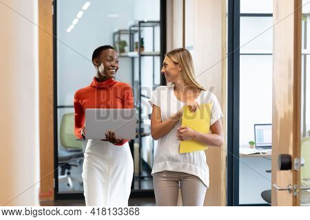 Happy diverse female business colleagues walking through corridor holding documents and talking. business in a modern office.