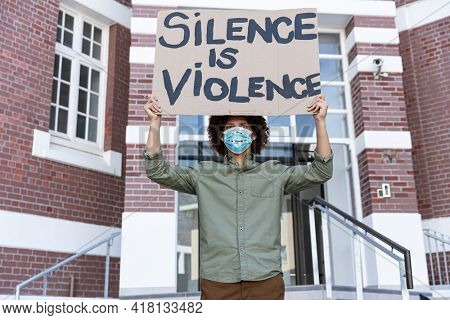 Portrait of mixed race man wearing a face mask holding placard. equal rights and justice protestors on demonstration march during coronavirus covid 19 pandemic.