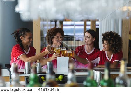 Diverse group of male and female sports fans raising glasses and watching game at bar. sports fan friends socialising and drinking at bar.