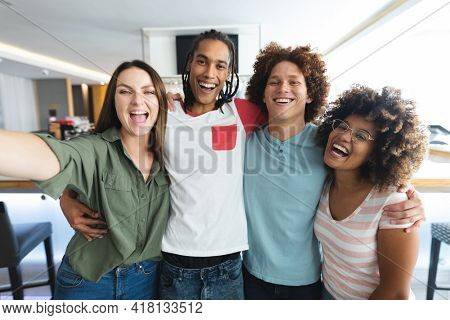 Diverse group of male and female friends taking selfie at bar. friends socialising and drinking at bar.