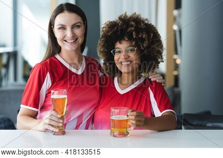 Portrait of two diverse female sports fans having beer smiling at bar. sports fan friends socialising and drinking at bar.