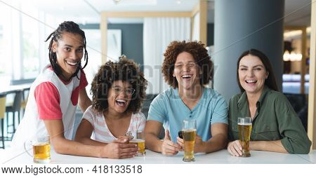 Portrait of group of male and female friends smiling at bar. friends socialising and drinking at bar.