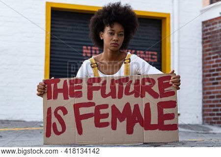 Portrait of mixed race woman holding placard. equal rights and justice protestors on demonstration march.