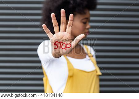 Portrait of mixed race woman making stop gesture with hand covered in writing. equal rights and justice protestors on demonstration march.