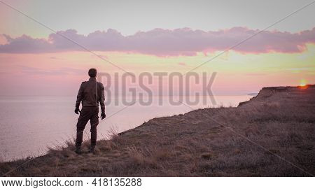 Looking On Young Biker In Leather Suit Stay On A Precipice Above Sea In Sunset