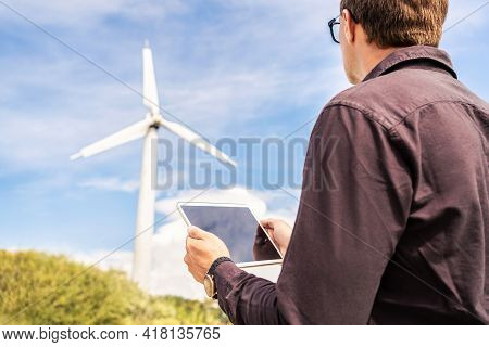 Engineer And Tablet In Wind Power Field Working For Renewable Sustainable Energy. Technician In Indu