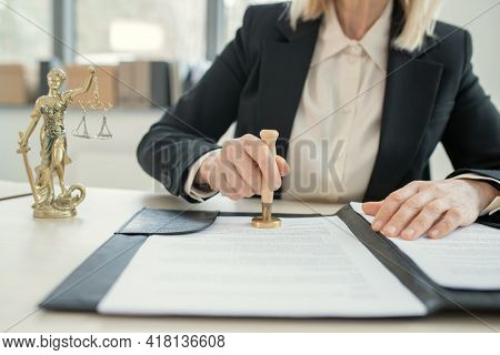 Close-up of unrecognizable female lawyer in black suit sitting at desk with themis statute and stamping document