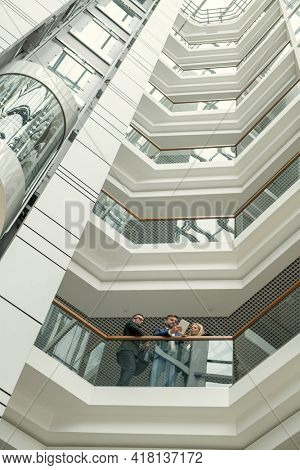 Below view of concentrated business people standing at railing and analyzing online document on tablet in modern office center
