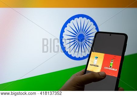 Man Holding A Mobile Phone Selecting Covaxin And Covishield In Front Of India Flag As Innoculation A