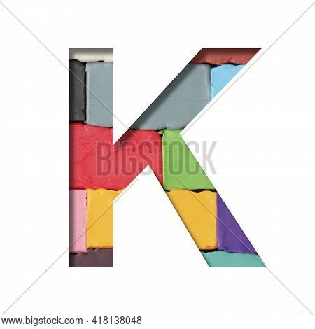 Multi-colored Plasticine Font. Letter K Cut Out Of Paper On A Background Of Pieces Of Colored Plasti