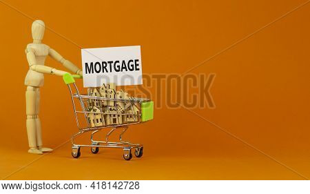 Mortgage Symbol. Miniature Shopping Cart With Wooden Houses, The Word Mortgage. Wooden Model Of Huma