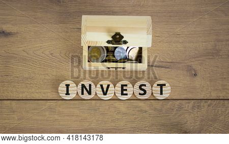 Invest Symbol. Concept Word Invest On Wooden Cubes On A Beautiful Wooden Background, Small Wooden Ch