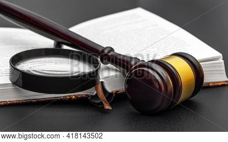Judge's Gavel With Magnifying Glass And Book On Black. Juristic Concept.