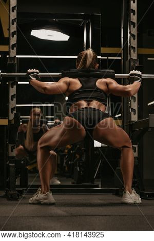 A Photo From Behind Of A Sporty Woman With Blonde Hair Who Is Squatting With A Barbell Near The Squa