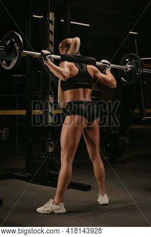 A Photo From Behind Of A Sporty Woman With Blonde Hair Who Is Started Squatting With A Barbell Near