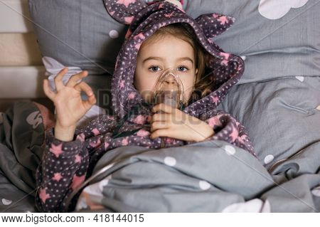 A Little Girl Is Being Treated For A Cough At Home Using An Inhaler. The Child Is Dressed In A Robe