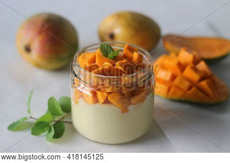 Vanilla Custard Topped With Fresh Cut Mangoes Served In A Jar