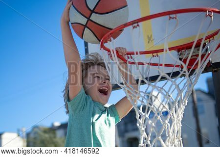 Closeup Face Of Kid Basketball Player Making Slam Dunk During Basketball Game. The Child Sport Playe