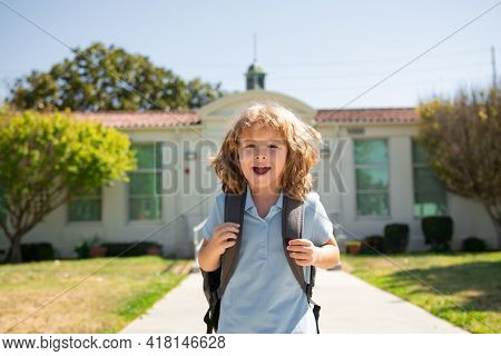 Funny School Boy Face. Child Pupul With Rucksacks In The Park Near School. Schoolboy With Backpacks