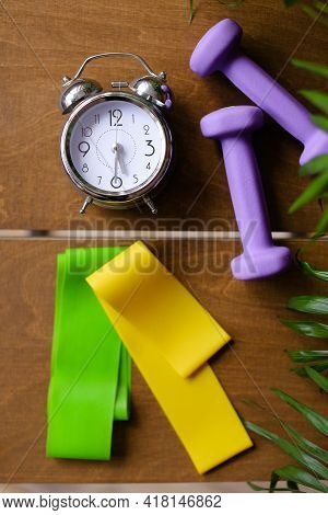 Alarm Clock And Women Dumbbells Lying On Wooden Table.