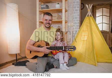 Portrait Of A Happy Father With A Guitar In His Hands And A Little Girl Sitting On Her Father's Lap