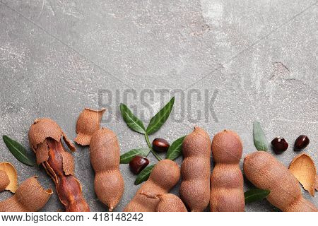 Ripe Tamarinds And Fresh Leaves On Grey Table, Flat Lay. Space For Text