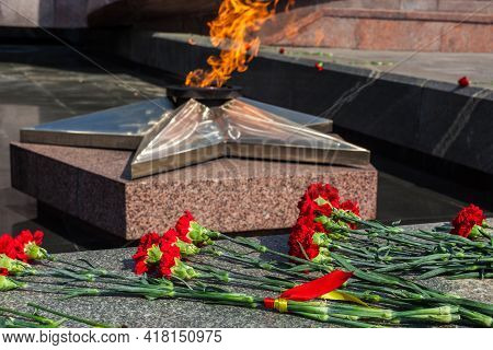 Victory Day On 9 May, Carnations Flowers At Eternal Fire Monument In Honor Or Memory Of The Fallen S