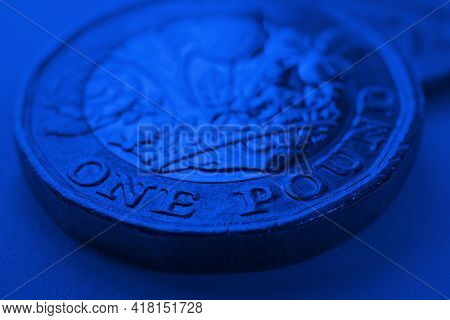 1 One British Pound Coin Close-up. Deep Blue Background Or Backdrop On An Economy, Business, Financi