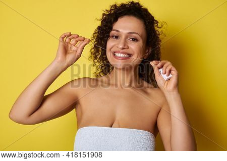 Smiling Young Woman Taking Care About Her Teeth By Using A Dental Floss For Cleaning Dental Cavity,