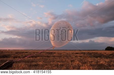 Silhouette Of Female Hand Holding Balloon With Hearts Against Sundown Purple Sky