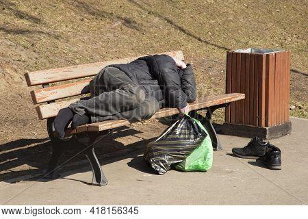 A Homeless Man Lies On A Bench On A City Street.