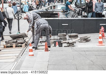Moscow , Russia - April 2021: Road Workers In Gray Uniform Repair The Road. Pit Removal And Patching