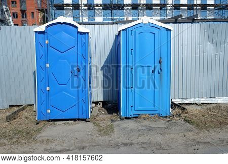 Plastic Mobile Dry Closets On A Construction Site For Workers Against The Background Of A Metal Temp