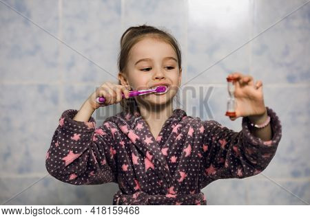 Little Cheerful Girl Brushes Her Teeth With Toothpaste With An Hourglass Timer. From Childhood, Pare