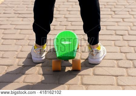 A Teenager Learns To Ride A Skateboard Or Penny Board On The Street. Legs And Skateboard Close Up. R
