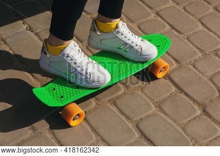 A Child On Vacation Rides A Green Skateboard Or Pennyboard In The Park. The Health Benefits Of Outdo